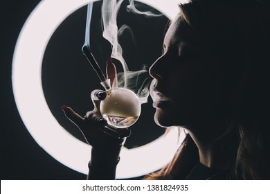 Woman smoking weed with contrast lighting