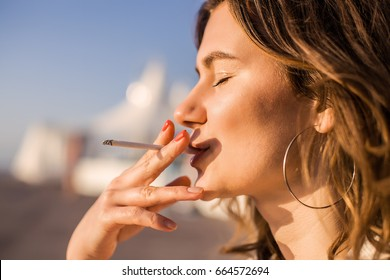 Woman smoking.cigarette,bad health,close eyes,earrings,curly hair,bad woman,close up portrait