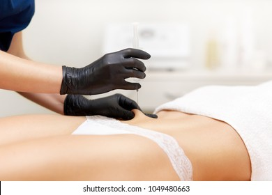 Woman with smooth skin having injection in her abdomen. Cosmetology therapist holding syringe in hands with black gloves, doing anticellulite and lifting treatment in modern beauty clinic.
