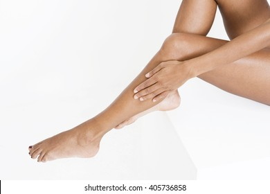 A woman smoothing moisturising lotion onto her legs