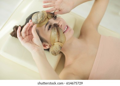 A woman with a snail on her face