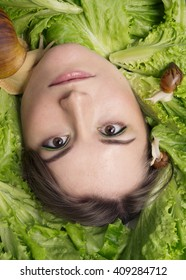 woman and snails among green salad leafs