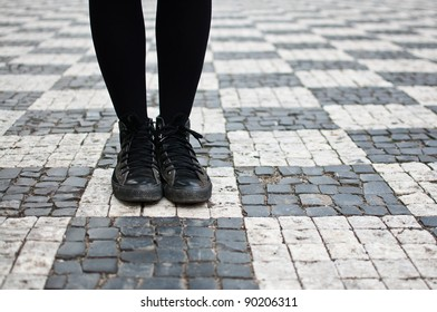 Woman in sneakers on the streets of Prague, on checkered pavement. Youth guidance, student guide, choose path concept, strategic planning.
