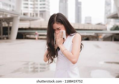 ํYoung woman sneeze on street because pollution,Young female got nose allergy