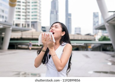 Woman sneeze on street because pollution outdoor,Young female got nose allergy