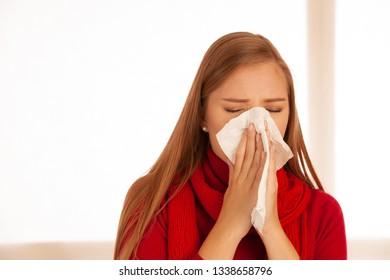 woman sneezes holding a handkerchief nasal .