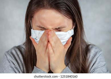 Woman sneezes in a medical mask
