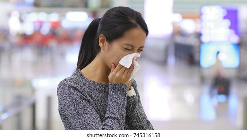 Woman sneezing the airport
