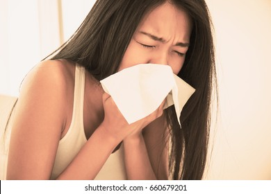 Woman sneezing in her bed, using tissue paper