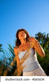 woman sneezing outdoor on a field over blue sky