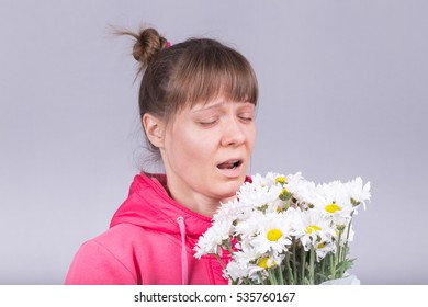 Woman sneezing over a bouquet of white flower. Hay fever concept