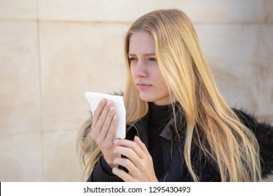 Woman sneezing in winter with hanky in hand