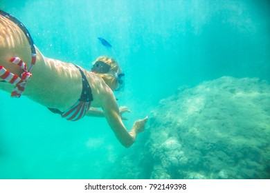 Woman snorkeler swims in tropical sea with american flag bikini. Underwater scene of a female apnea and doing skin diving. Watersport activity in Hawaii. Tropical destination holiday travel.