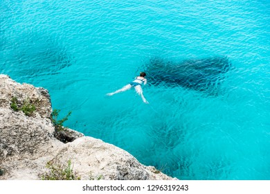 Woman snorkeling in blue water, Curacao