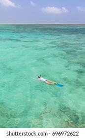 Woman snorkeling in clear shallow sea of tropical lagoon with turquoise blue water and coral reef, near exotic island. Mnemba island, Zanzibar, Tanzania.