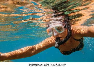 Woman snorkeling. Female diver wearing diving mask swimming in sea.