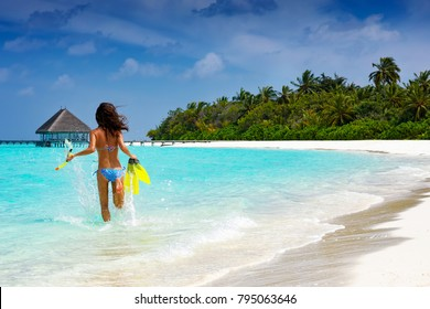 Woman with snorkeling gear running into the turquoise, tropical waters of the Maldives