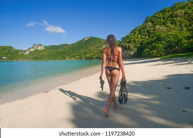 Woman with snorkeling gear walking into the turquoise, tropical waters of the separates sea Ang Thong National Marine Park Koh Samui Suratthani