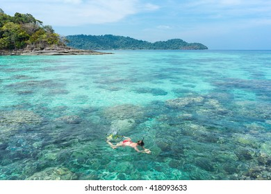 Woman snorkeling in Ko Surin tropical Island paradise with clear blue water and stunning coral reef, Phang Nga, Thailand