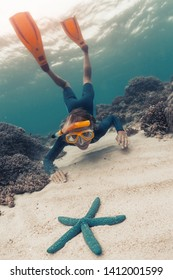 Woman snorkeling and skin diving in the tropical sea and gets closer to the blue starfish lying on the sandy bottom. Focus on the model's face