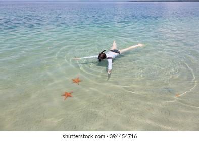Woman snorkeling in transparent sea above starfish, Panama