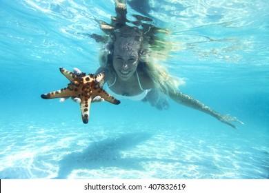 Woman is snorkeling underwater, showing starfish