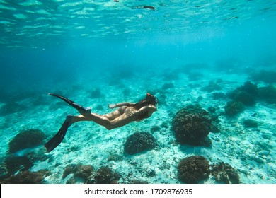 Woman snorkelling underwater with snorkel mask in clear transparent water in beautiful tropical lagoon with coral reef. Freediving activity. Leisure on vacations.