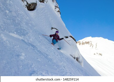 Woman Snow Skier on a wild, steep slope with Mountain View