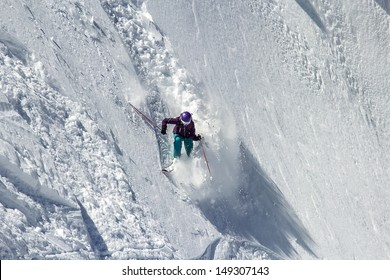 Woman Snow Skier twist on a very steep slope. Starts a small avalanche - slide