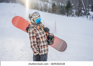 Woman snowboarder on a sunny winter day at a ski resort wearing a medical mask during COVID-19 coronavirus