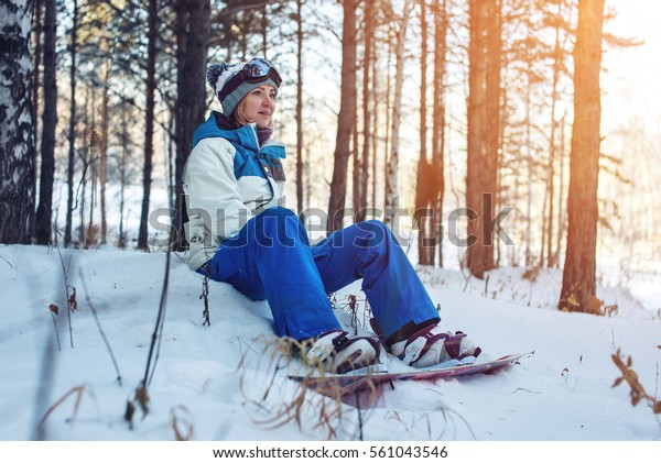 woman snowboarder with the snowboard is resting sitting on the snow among the trees on sunset background, concept of sport and active lifestyle