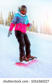 Woman snowboarding in glasses, helmet, blue and pink jacket in sunny day