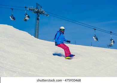 Woman snowboarding on a sunny day in the ski resort of Livigno - Italy