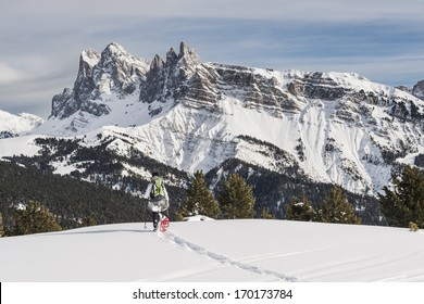 Woman snowshoeing against Dolomites in Winter