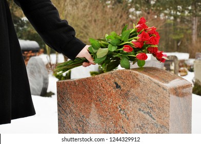 Woman in a snowy graveyard in winter puts a bouquet of roses on a tombstone of grave