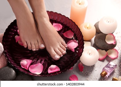 Woman soaking her feet in bowl with water and rose petals on grey floor, closeup. Spa treatment