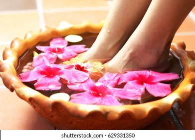 Woman soaking her feet in a bowl of flower water