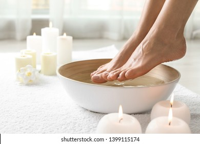 Woman soaking her feet in dish indoors, closeup with space for text. Spa treatment
