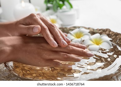 Woman soaking her hands in bowl of water and flowers on table, closeup with space for text. Spa treatment