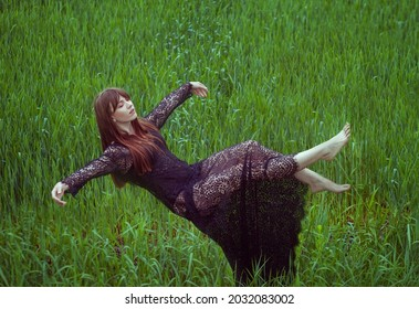 The woman soars in the air, lying as if in a dream. She hovers over a green field of grass. She levitates outdoors.