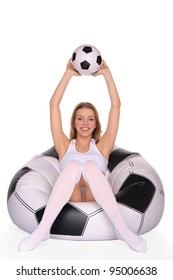 woman with soccer ball on an inflatable chair isolated on white