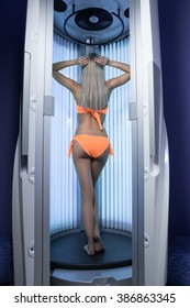 The woman in Solarium. Woman gets tanning standing. Her bright bathing suit orange. Turned backwards