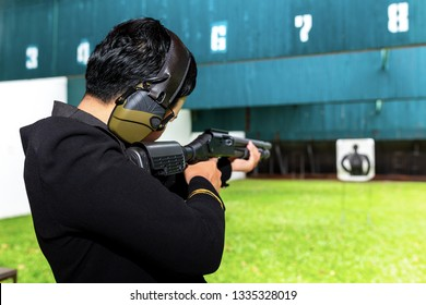 A woman soldier with law enforcement aim a long shotgun to target in martial arts for self defense in an emergency case. Shooting gun by two hand in academy shooting range.