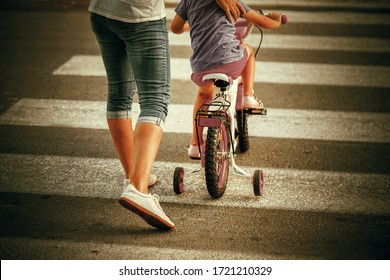 Woman with son crossing the road in the city. Mother goes pedestrian crossing with childr on bicycle. Back view.