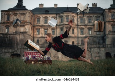 Woman sorceress reads book and flies in air against backdrop of ancient castle. Levitation. Around her fly books in air.