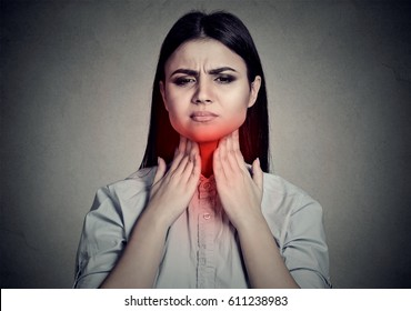 Woman with sore throat touching her neck colored in red isolated on gray wall background