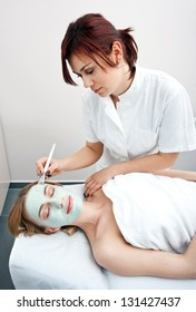 woman in spa applying beauty mask on her face
