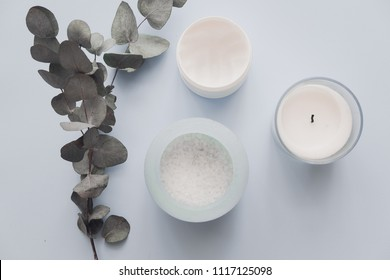 Woman spa beauty products on pastel blue backround from above. Body, face, hair sugar salt scrub, candle, eucalyptus. Minimalism blogging concept