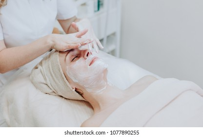 Woman at spa cosmetics professional procedures. Applying cosmetology mask.