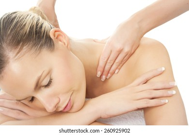 Woman in spa getting shoulders massage. Relaxation concept over white background.